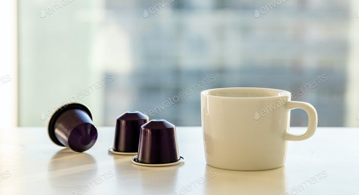 Espresso coffee cup and coffee capsules on a white table. Blur window background