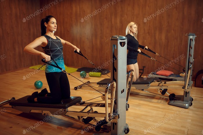 Two women on pilates training in gym, flexibility
