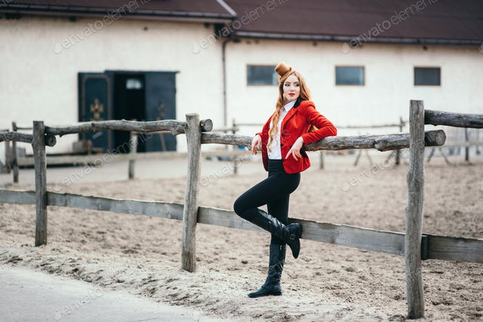 red-haired jockey girl in a red cardigan and black high boots