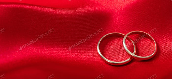 Two golden wedding rings on red satin background, banner, copy space