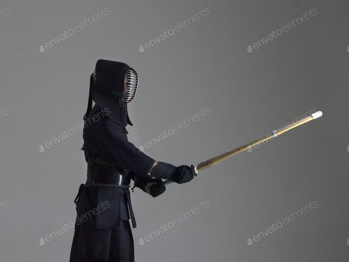 Portrait of man kendo fighter with shinai. Studio shot