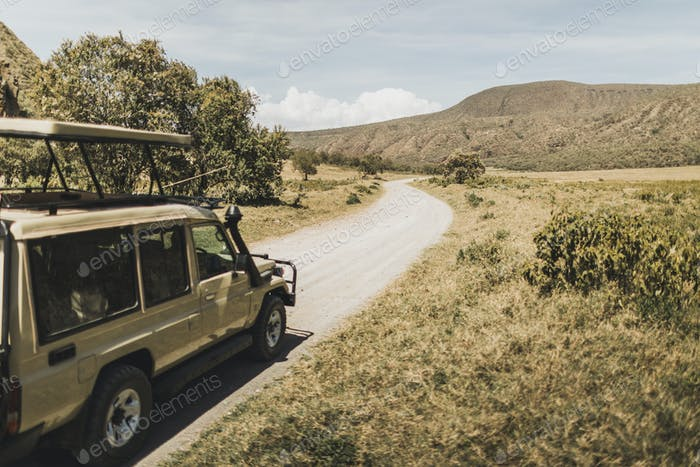 Safari in Hell's Gate national park in Kenya. Off road jeep car, savannah and mountain view