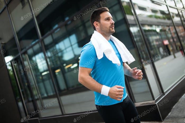 Attractive fit man running and exercising in the city