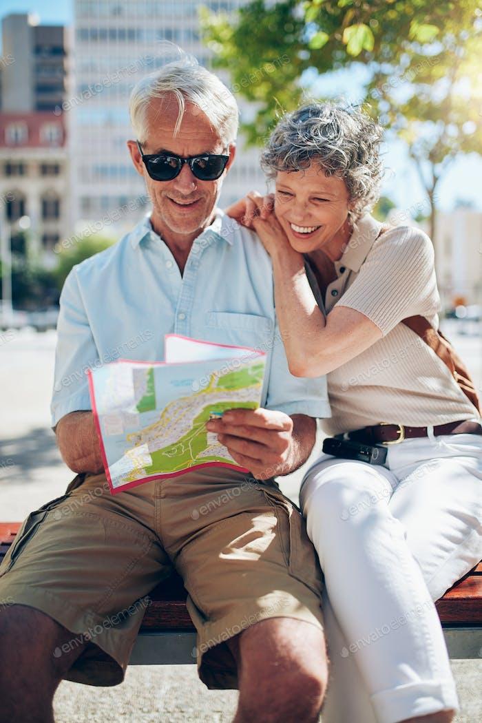 Mature tourist reading city map