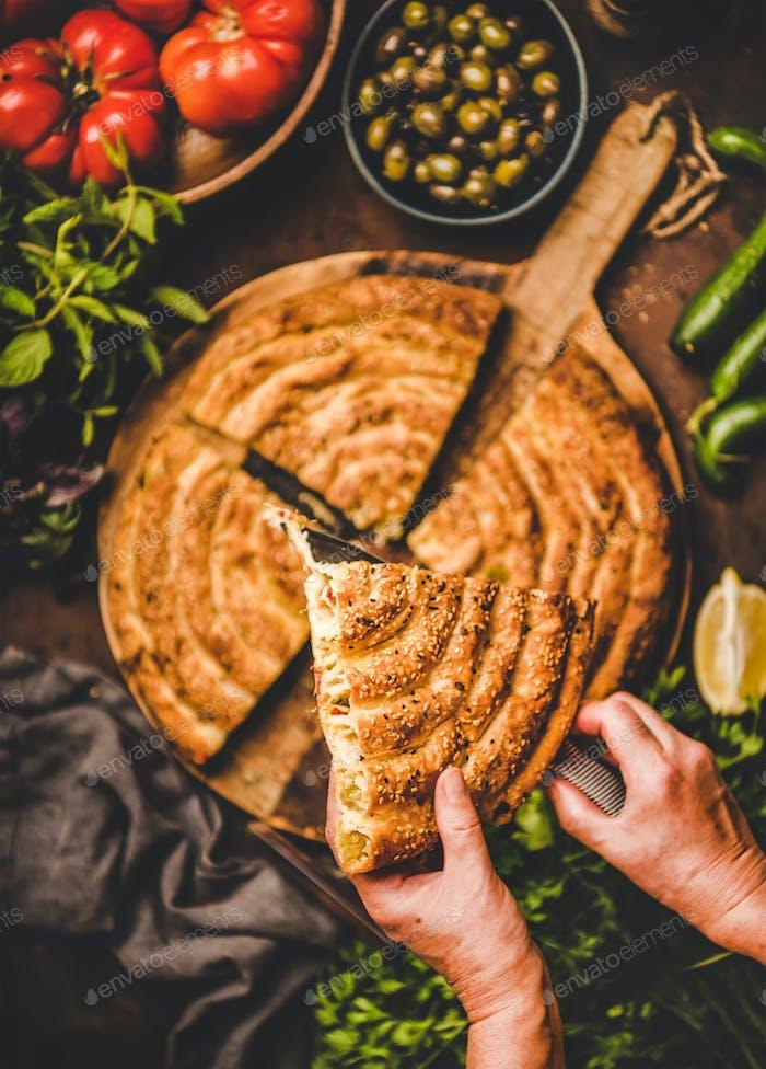 Menschliche Hände halten Stück türkischen Borek Kuchen mit Spinat