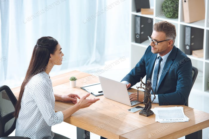 high angle view of lawyer working with client in office
