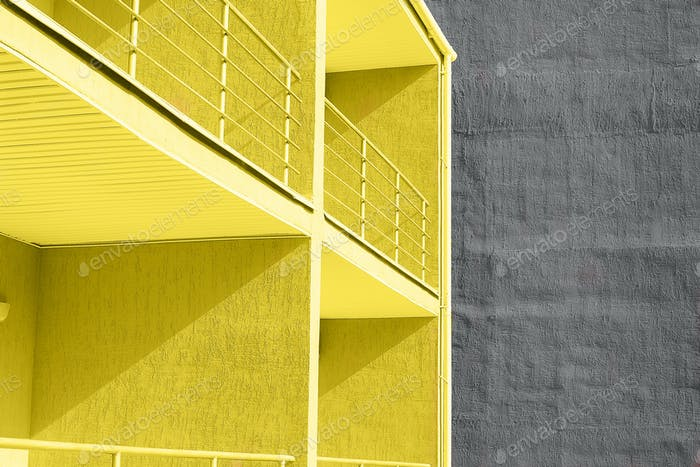 View of yellow and gray wall texture concrete buildings with balcony. Concept of color of 2021 year