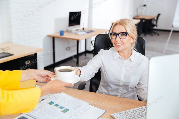 Secretary bringing cup of coffee for her boss in office