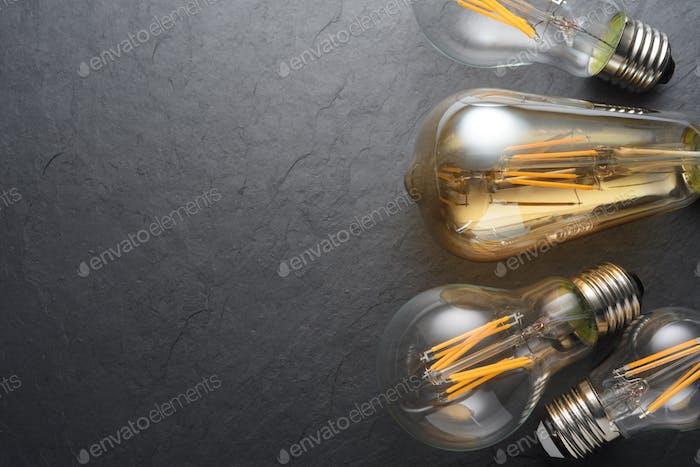 Transparent LED filament light bulbs on black background.