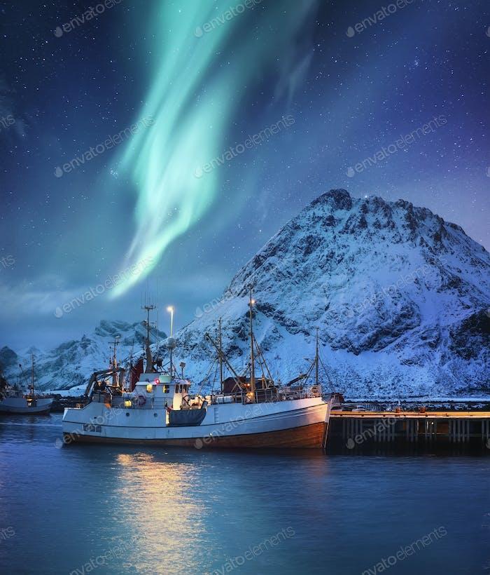 Nordlicht, Berge und Fischerboot. Aurora Borealis, Lofoten Inseln, Norwegen.