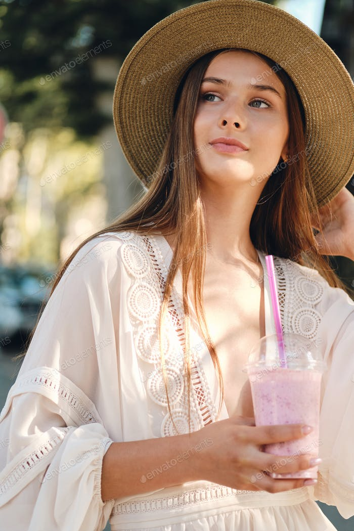 Young girl in white dress and hat holding smoothie dreamily looking aside on cozy city street