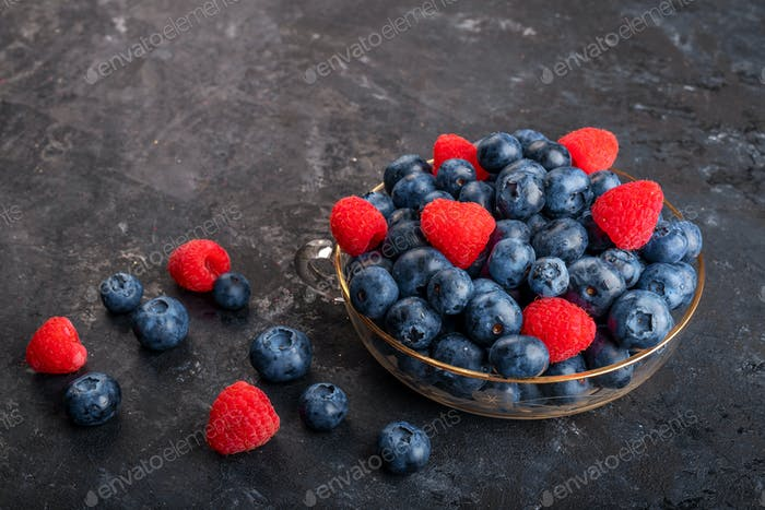 Fresh blueberries and strawberries in a glass bowl on dark background
