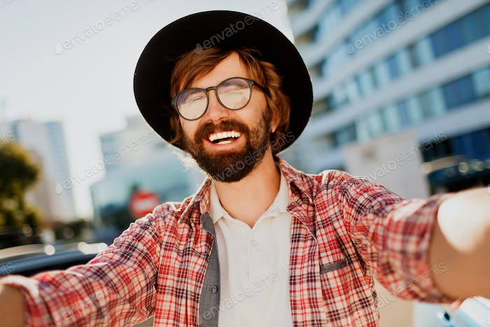 Funny man with beard making self portrait by camera