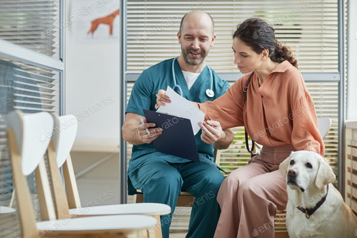 Young Woman Consulting Veterinarian