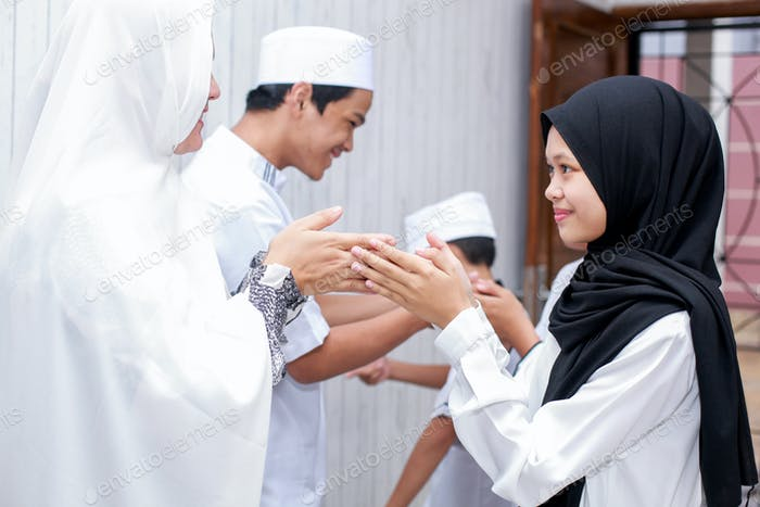 Muslim family shaking hand for forgiving each other on eid mubarak