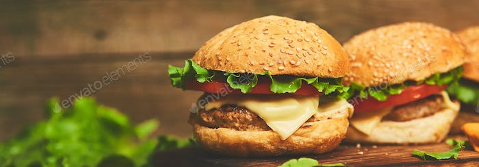 Banner of Craft beef burger on wooden table isolated on black background.