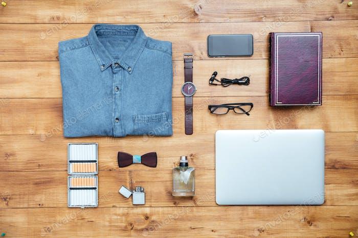 Travel concept shirt, mobile phone, earphones, laptop, perfume, eyeglasses, watch