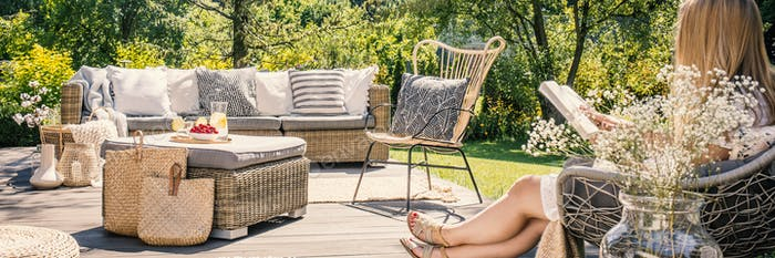 Woman reading a book on patio with rattan table, chair and sofa