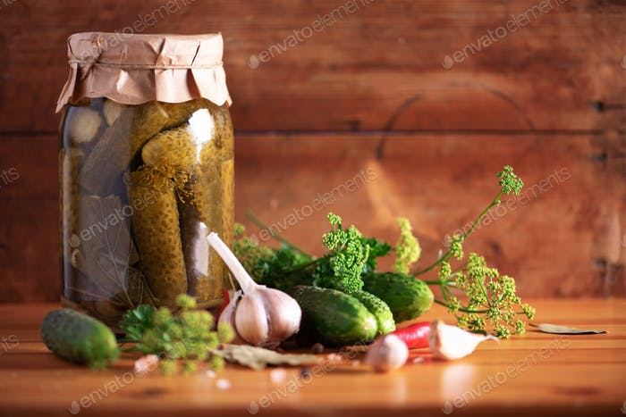 Canned gherkins in jar, fresh dill, garlic, pepper over wooden background. Copy space. Harvest