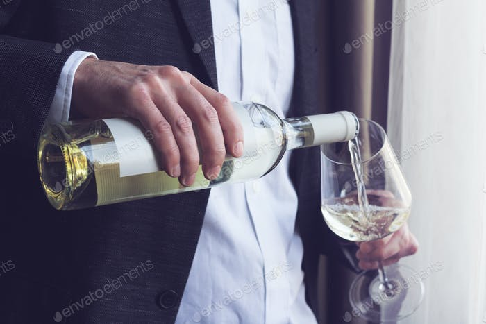 Man pouring white wine into a glass