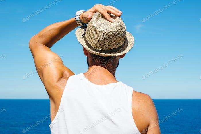 Mann hält Hut Blick auf Ozean