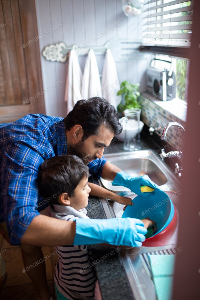 Father assisting son for cleaning utensils at home