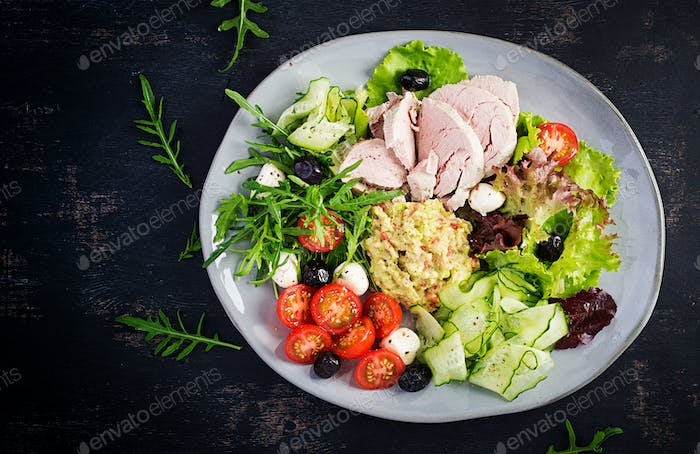 Dinner dish with boiled pork meat, avocado guacamole, tomatoes, cucumbers, mozzarella cheese