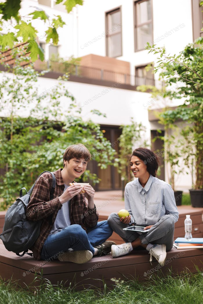 Young couple of students sitting on bench with sandwich and green apple