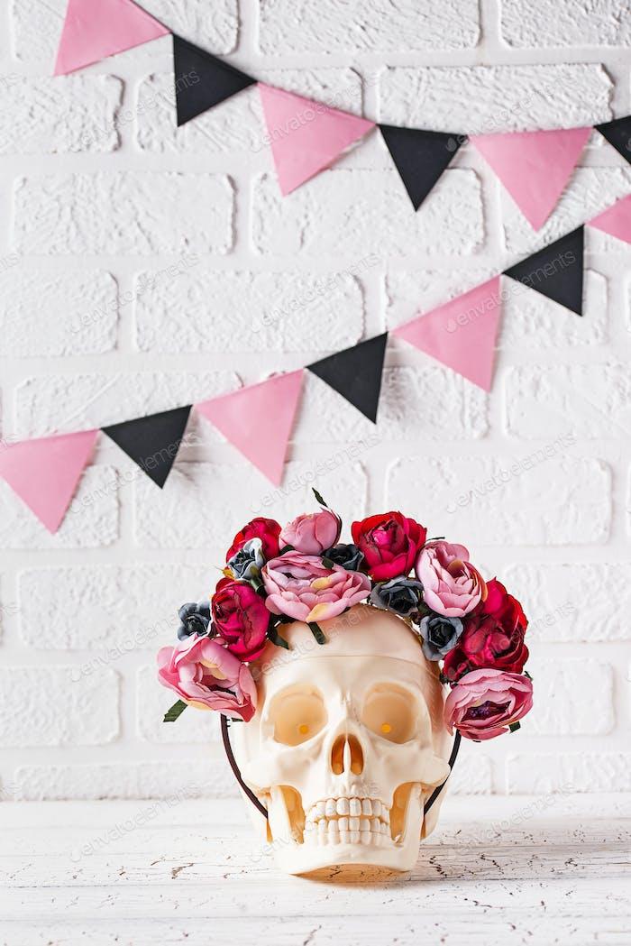 Schädel mit Kranz aus rosa Blüten