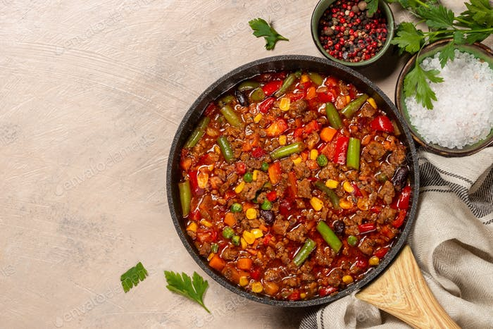 Chili con carne in skillet on light stone table