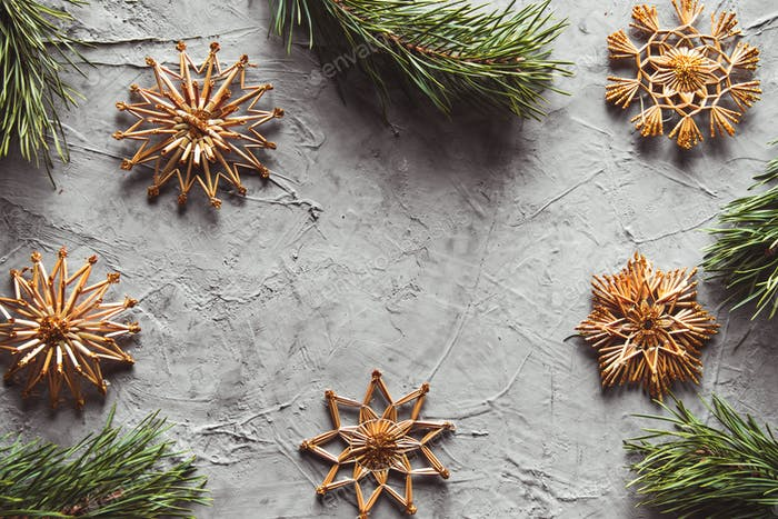 Homemade straw decor on Christmas tree close up. on a gray concrete background