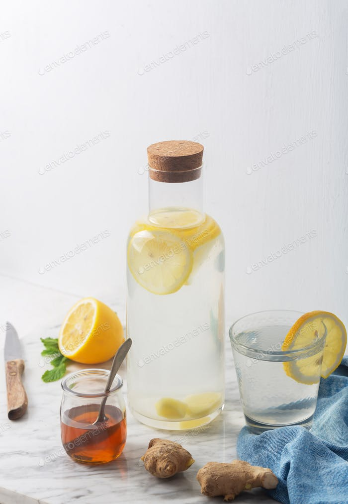 Ginger Water and its Ingredients, Such as Lemon and Honey, Vertical Orientation