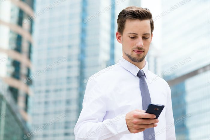 Caucasian businessman using the smartphone at outdoor