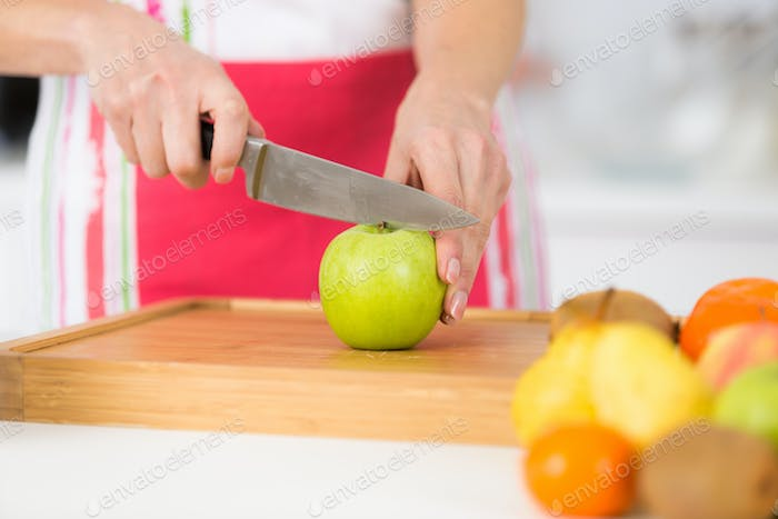close-up on mature female hands slicing apples on chopping board