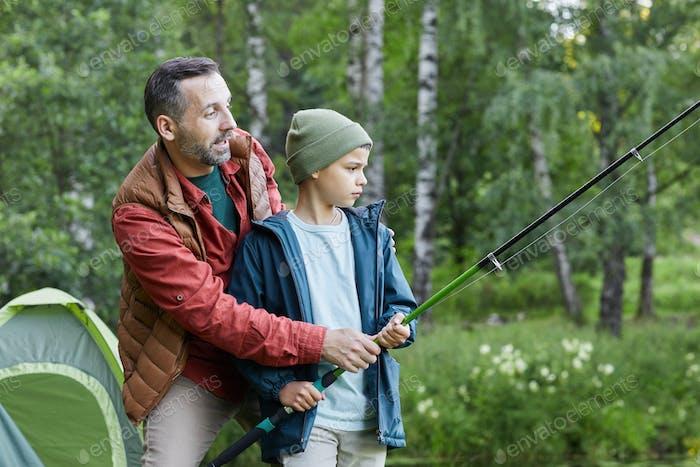 Father Teaching Little Boy Fishing by Lake