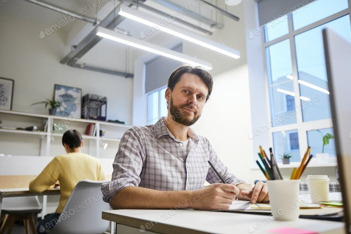 Content male designer working on project