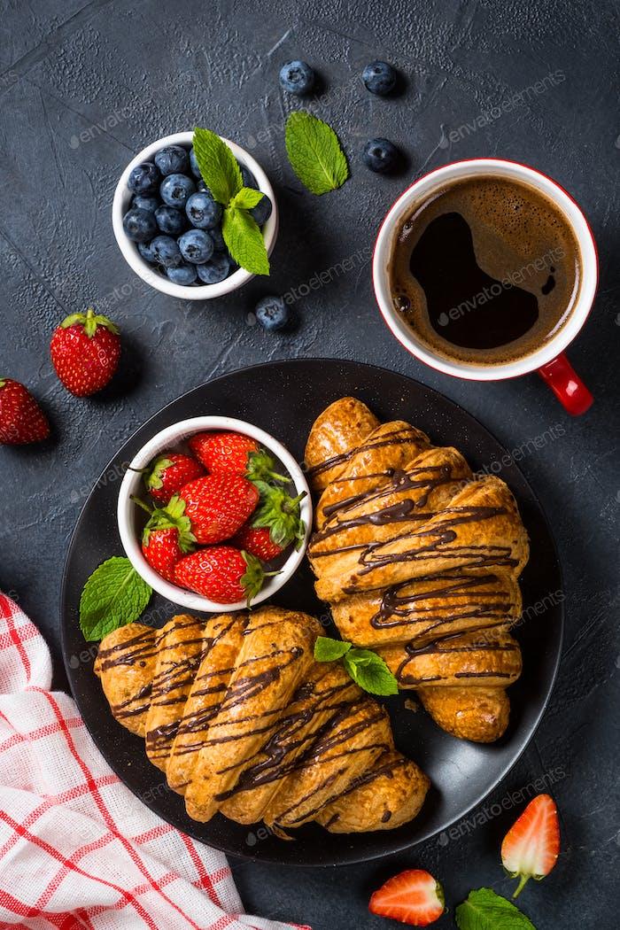 Croissant mit frischen Beeren und Tasse Kaffee auf schwarz