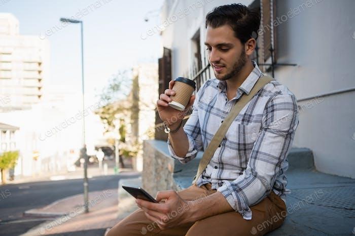 Smiling man having drink while using mobile phone