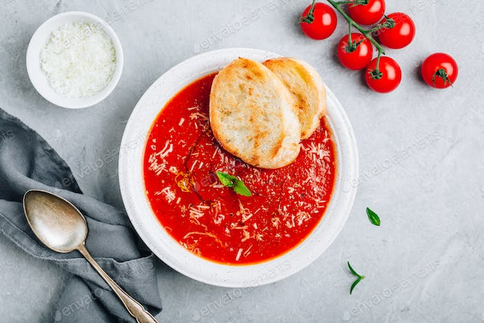 Tomato basil soup with parmesan cheese and bread toasts on gray stone background