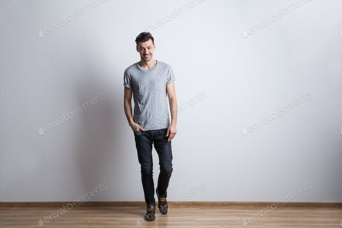 Full length portrait of a young man in a studio. Copy space.