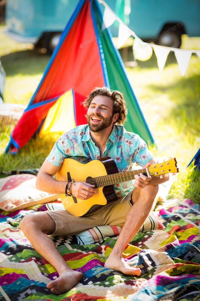 Man playing guitar at campsite