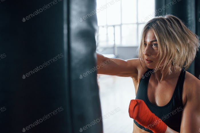 She can defend herself. Female boxer is punching the bag. Blonde have exercise in the gym