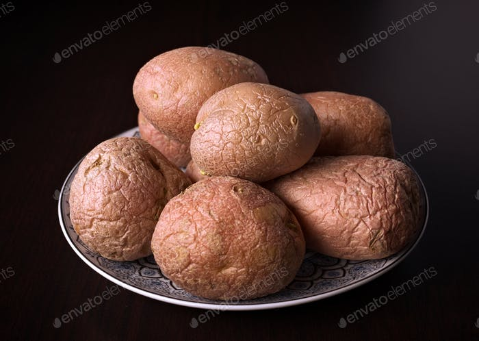 group of whole potatoes uncooked on classic wooden background