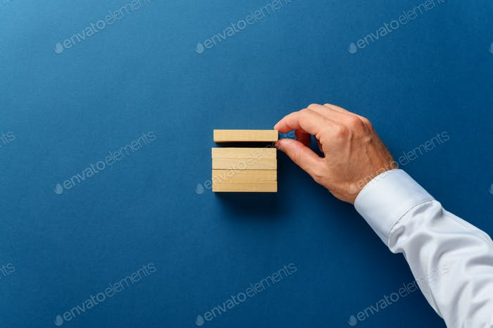 Hand of a businessman stacking wooden pegs