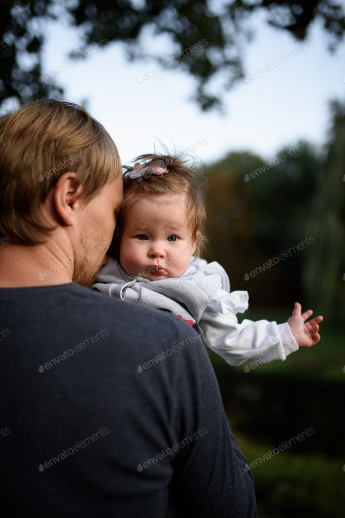 Young father having fun with his little daughter in park