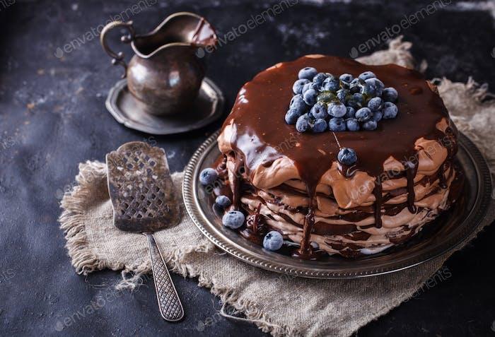 Schokoladenkuchen aus Schokoladen-Pfannkuchen mit Zuckerguss, mit Blaubeeren.