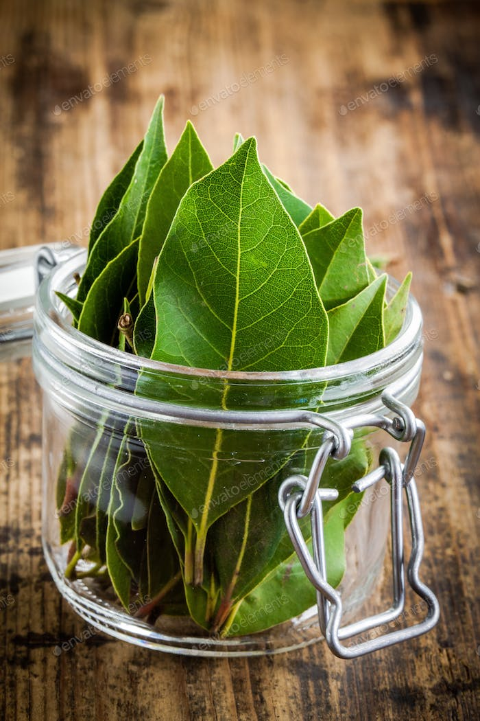 Fresh bay leaves in a glass jar on a wooden background