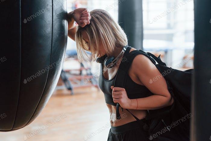 Müssen Sie sich nach langer Straße ausruhen. Erwachsene weiblich mit schwarzer Tasche und Kopfhörern im Fitnessstudio