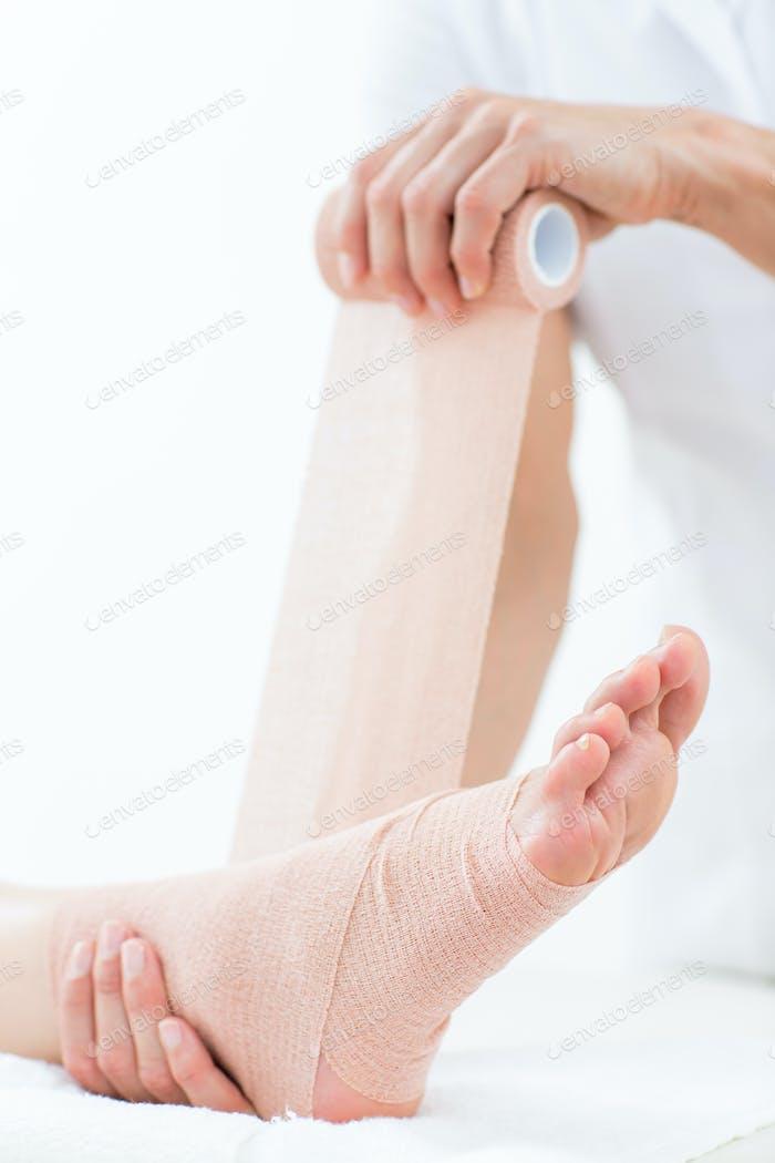 Medicina vendar su paciente tobillo en el consultorio médico