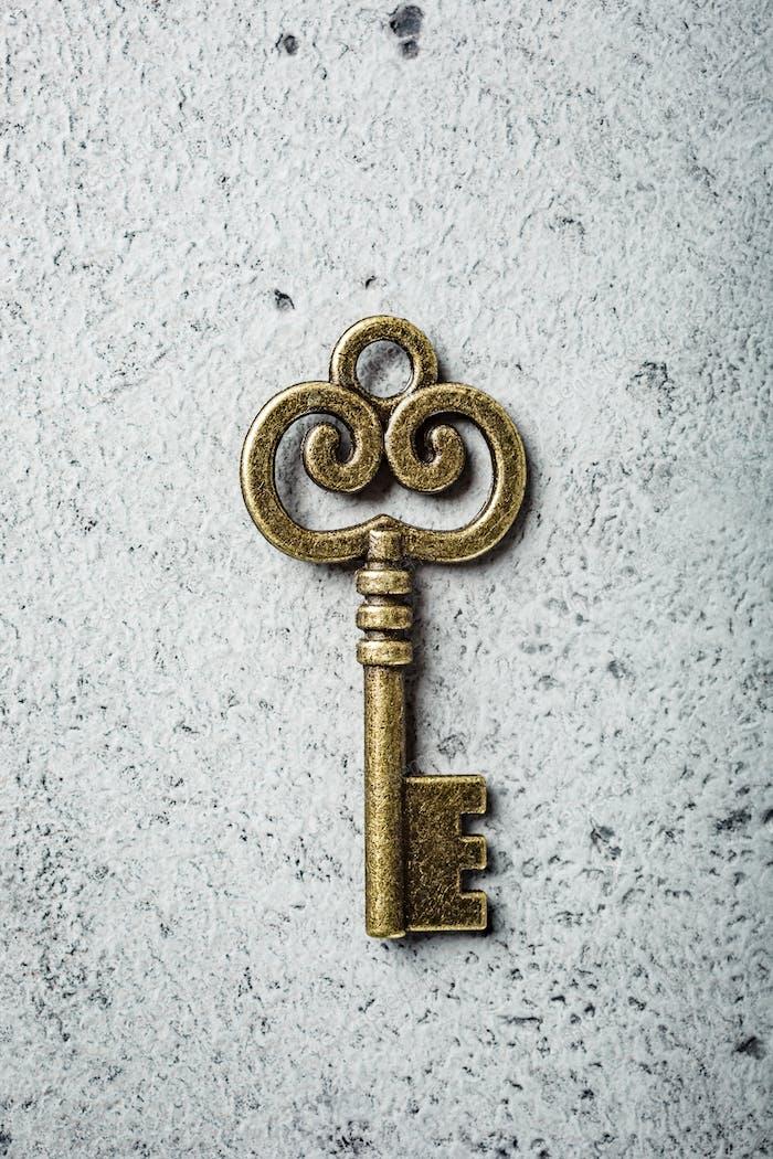 Alter Schlüssel auf alten grauen Betonhintergrund.